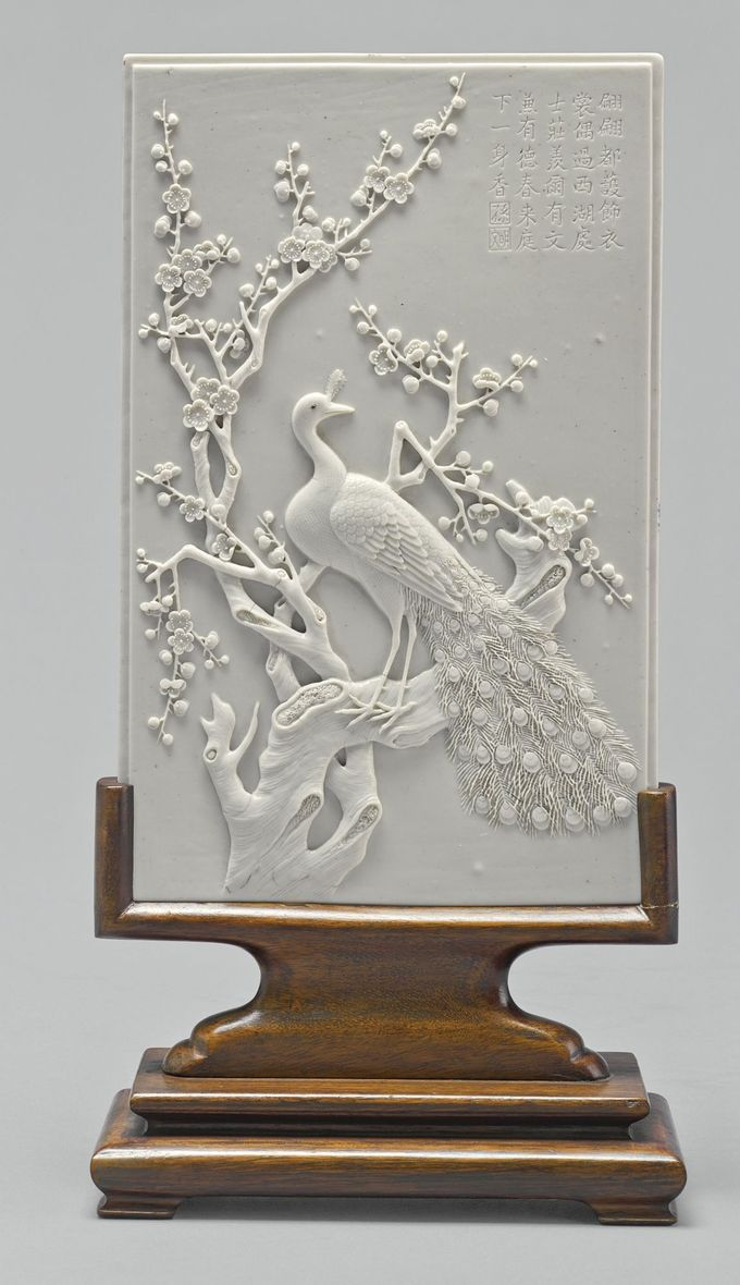 A WHITE BISCUIT GLAZED 'PEACOCK AND PRUNUS' PORCELAIN PLAQUE<br>20TH CENTURY | lot | Sotheby's