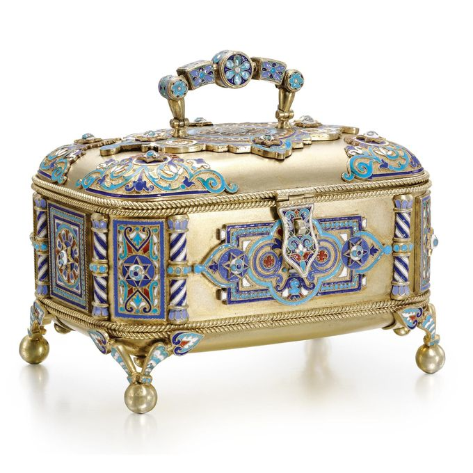 A silver-gilt and cloisonné enamel box, Sergei Nazarov, Moscow, 1888, rounded rectangular form, the surface applied with raised panels of enamelled geometric motifs and scrolls, the corners with columns, on four ball feet below openwork brackets, 88 standard, Austro-Hungarian import mark.
