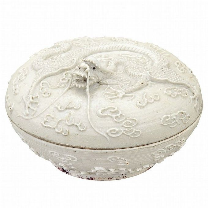 Chinese White Glazed Porcelain Seal Paste Box 19th Century Of circular form supported on a low foot, the domed cover worked with a sinuous five-clawed dragon, the head raised high with mouth open and long wiskers amidst stylized cloud wisps, the base with a band of turbulent waves. Diameter 3 3/8 inches.