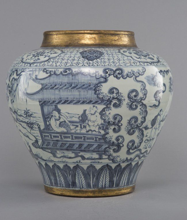 A LARGE BLUE AND WHITE JAR, Ming Dynasty. The jar is of globular-shaped and is decorated with a small porch occupied by a master and a servant surrounded by trees, grass and ruyi clouds. Overall the jar is of light blue colour tone. The neck of the jar is of golden colour. 16 1/2 in. tall.