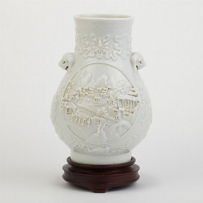 Chinese White Glazed Vase 19th Century The hu form molded and carved on the exterior with a village scene cartouche to either side, the neck set with lion head and linked chain handles, the base with an impressed Qianlong seal mark. Height 7 inches.