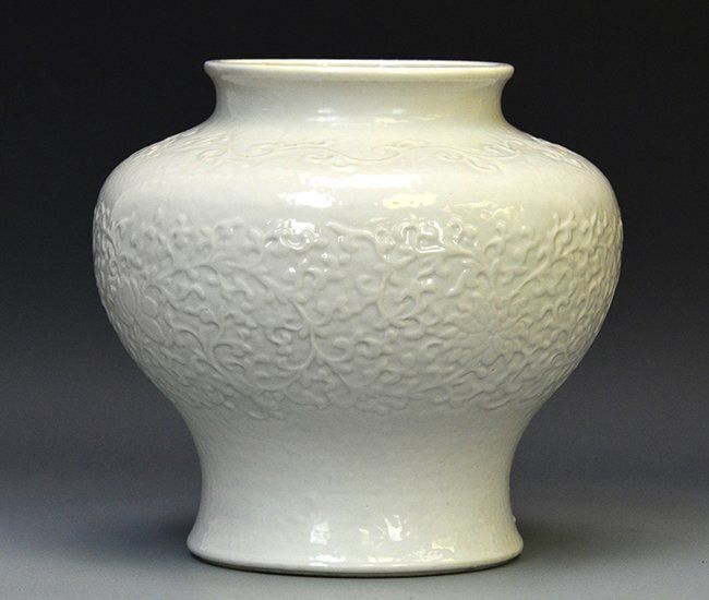 A Chinese White Glazed Porcelain Jar, 18th Century, the jar with a lotus bearing meander around the body with a vine border on the shoulder, with a crack to the base, appx. 7 3/4 in. H.