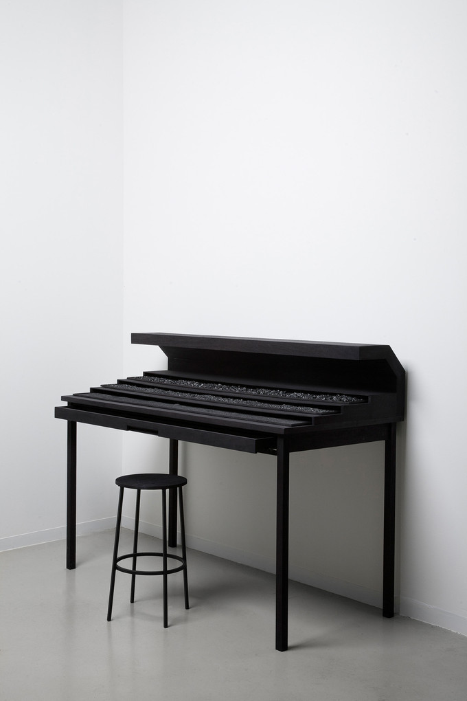 Workspace I, 114 x 65 x 118cm, walnut wood, black ink, light, coal, 2016The Exhibitions 'The Foundation' and 'The Monolith 'encompasses the artist's multi-disciplinary practice which spans large scale installation, drawings, video, sculpture and photography and follows on from his much acclaimed solo show - entitled 'The Relativity of Matter' - at the Marres House for Contemporary Culture in Maastricht.On the occasion of this gargantuan undertaking, Van Veluw had been working for more than a year on an immersive installation consisting of constructing a building within the period building of the museum.Visitors entered alone into this alternative reality. From room to room, the person is plunged into an ever stranger world and confronted by seemingly different forms of primal matter. Levi's two long-term previous projects, 'The Origin of the Beginning' and 'The Collapse of Cohesion' represent previous instalments in the artist's fascination with creating parallel universes.......