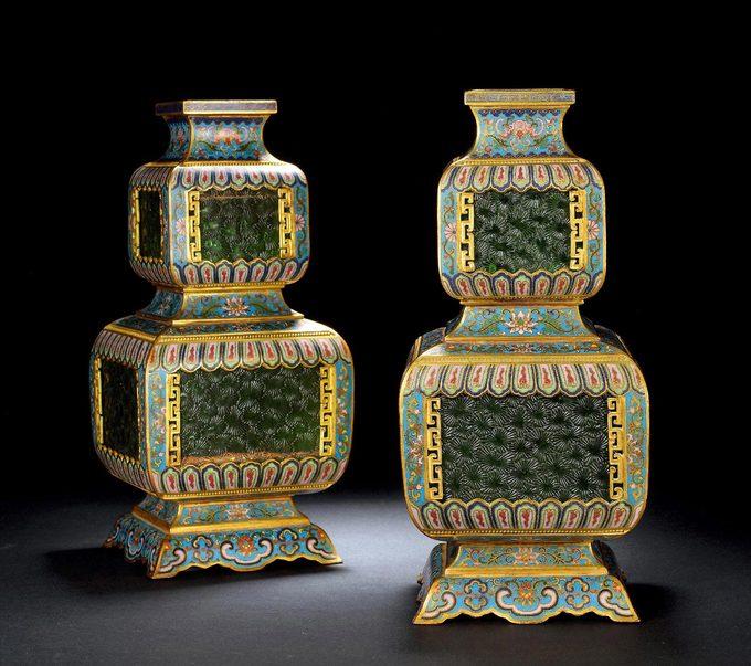 """【清乾隆 铜胎掐丝珐琅花卉嵌透绿料宫灯 (一对)】灯身上下开光中还镶嵌了绿色透明玻璃料,玻璃古称琉璃,先秦时已用做贵重饰品,佛家以琉璃为七宝之一,释教东传后,玻璃更是备受珍视。但中国本土的玻璃配方长期落后于西方,上乘清透的玻璃一直依赖异域输送。清代称玻璃为""""料器"""",烧制水平远超前代,清康熙时宫中造办处设立""""玻璃厂"""",直接聘请欧洲传教士参与,引进先进的西方技术系统,大量制作宫廷珍玩器,品种丰富,工艺多样,所制玻璃器莹澈精巧,极受推崇。这对清乾隆掐丝珐琅花卉嵌透绿料宫灯所用玻璃料,质地均匀透澈,色泽翠绿如宝石"""