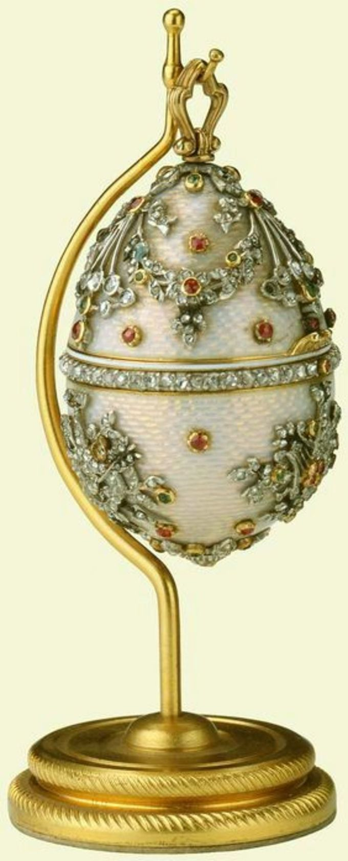 Egg, cream guilloché enamel set with diamond band around centre, upper section with ribbon swags, lower section with heart trophies, all set with rubies and emeralds, gold ring, hanging from plain gold stand, circular base with spiral pattern. Given to Qu