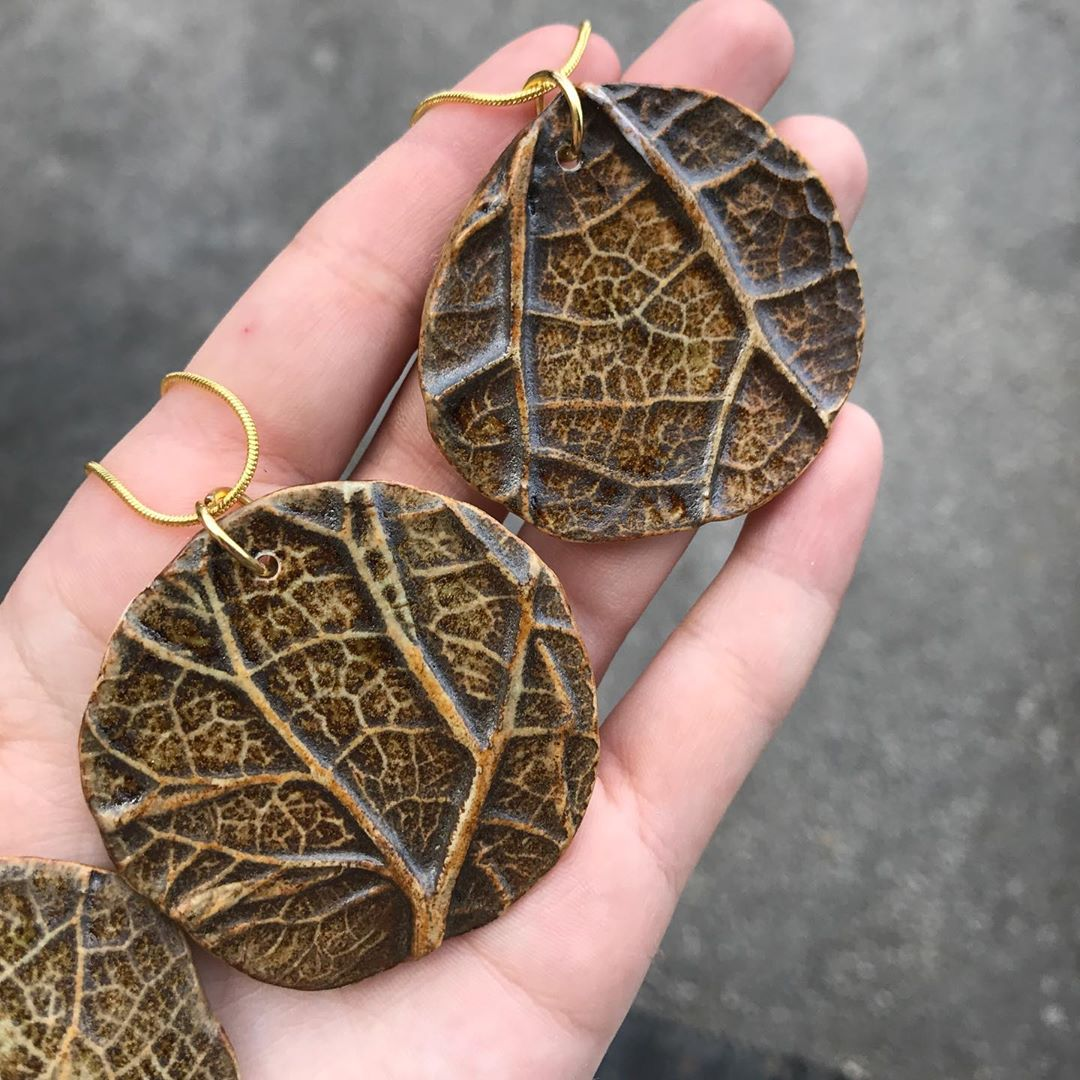 A few of the necklace pendants have been glaze fired! I envisioned them being more green than brown but I applied the glaze too thin. Although, they are growing on me  swipe through all the pics to see my awkward attempt at modeling one of the necklaces